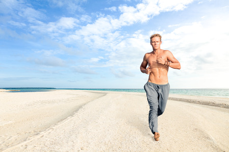 beach front: Man running on white sand of tropical beach