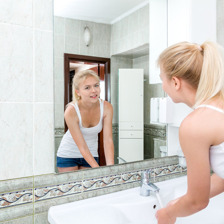 woman washing face: Young beautiful blonde woman washing face and hands