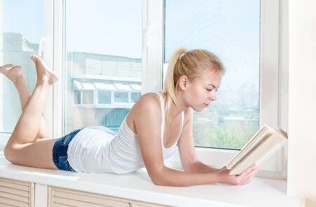 windowsill: Young woman read book sitting on windowsill