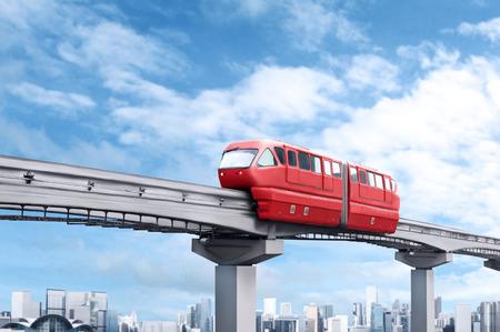 青い空とバック グラウンドで近代的な都市に対して赤モノレール列車 写真素材