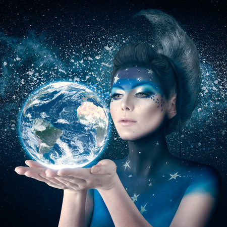 Woman like moon inspired bodyart and hairstyle holding planet earth in hand with care. Element of this planet furnished by NASA Archivio Fotografico