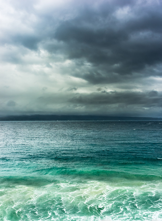 horizont: Heavy dramatic clouds over stormy sea with land on horizont