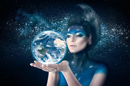 月のような女性は、ボディー アートや髪型注意して地球を手で押しにインスパイアされました。