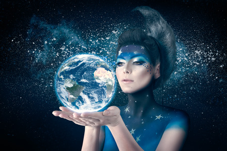 Woman like moon inspired body art and hairstyle holding planet earth in hand with care.