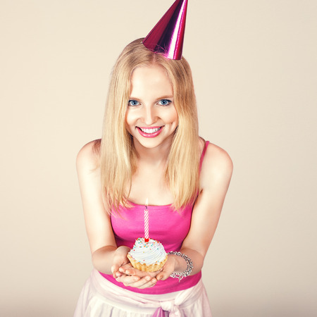 Young happy girl with birthday cake in hands photo