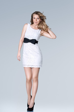 mini: Beautiful young slim woman in white mini dress full body studio portrait