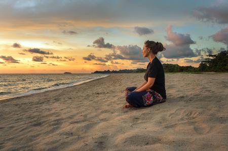 zen attitude: Femme assise sur le sable de plage et de détente à l'heure du coucher du soleil Banque d'images