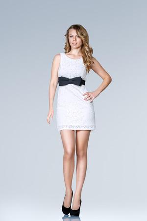 mini skirt: Joven y bella mujer delgada en blanco mini vestido de cuerpo completo retrato de estudio Foto de archivo