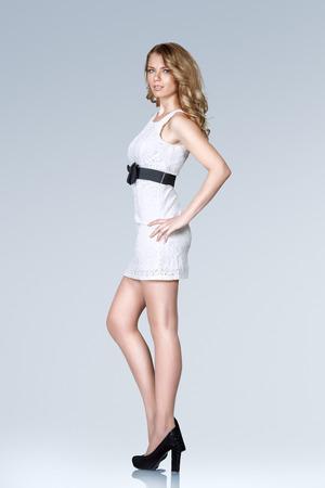 Beautiful young slim woman in white mini dress full body studio portrait