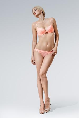 modelo desnuda: Joven mujer sexy en lencería posando sobre fondo gris Foto de archivo