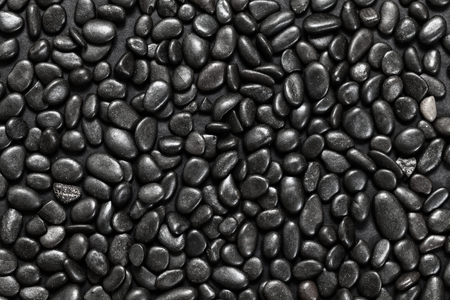 pebbles: Abstract background of black pebble stones arranged on black surface