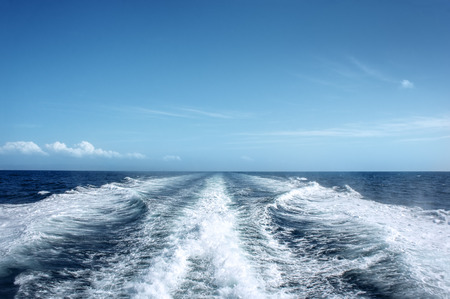 Trail on water surface behind of fast moving motor boat Stock Photo