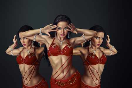 red dress: Beautiful belly dancer perfoming exotic dance in red flutter dress