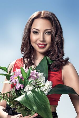 ramo de flores: Mujer hermosa joven con flores ramo retrato al aire libre Foto de archivo