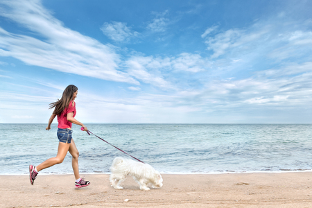 Young beautiful asian woman walking with dog near sea