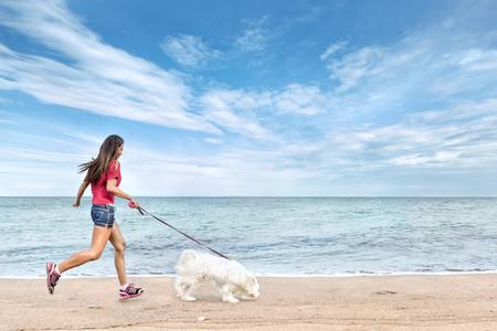 caminando: Joven y bella mujer asiática caminar con el perro cerca del mar