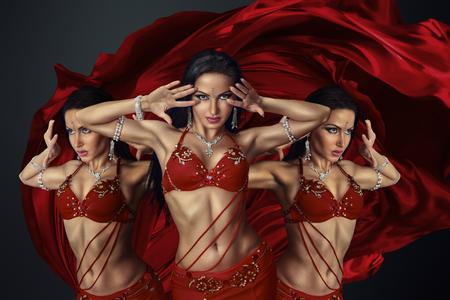 taniec: Piękna tancerka brzucha w perfoming egzotyczny taniec czerwonej sukni trzepotanie