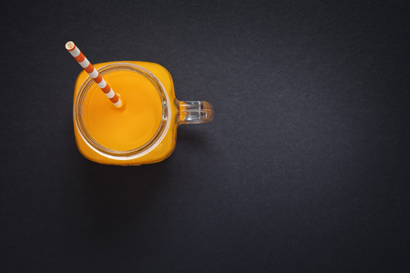 Fresh orange juice with drinking straw on dark gray background with space for text