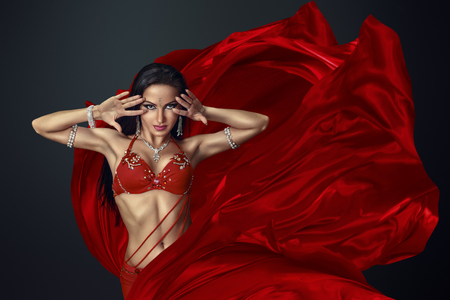 costume jewelry: Beautiful belly dancer perfoming exotic dance in red flutter dress