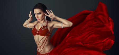 danseuse orientale: Belle danseuse du ventre perfoming danse exotique en robe rouge de flottement Banque d'images
