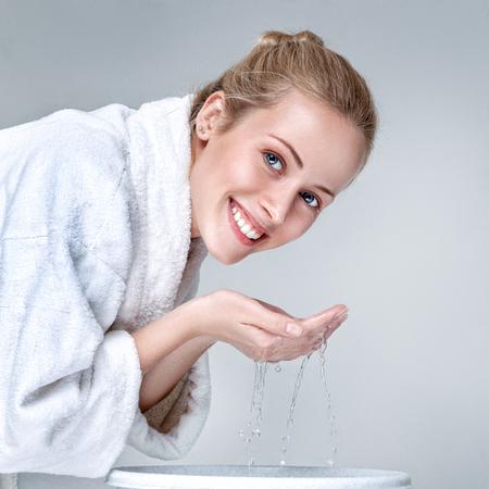朝のきれいな水で顔を洗う白いバスローブの若い女性