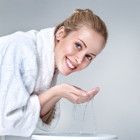 Young woman in white bathrobe washing face with clean water at morning