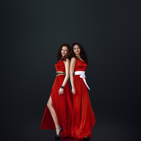 red dress: Two young beautiful woman in long red dress Stock Photo