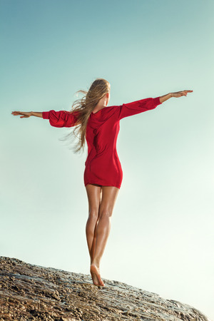 posing: Young sexy woman in red mini dress posing in front of sea Stock Photo