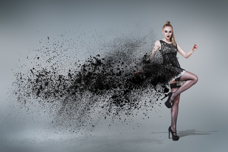 Young woman dancing inside cloud of dust