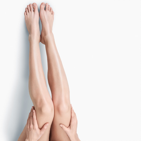 mujer celulitis: Hermosas largas piernas femeninas delgadas aisladas sobre fondo blanco