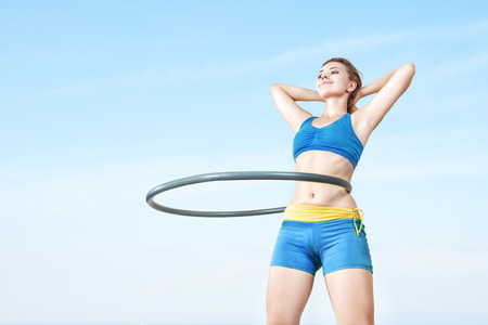 Young woman rotates hula hoop on nature background. Low angle view