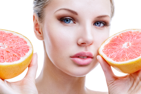fruit background: Young woman with grapefruit in hands isolated on white background