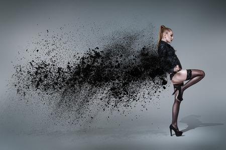 Young woman dancing inside cloud of dust