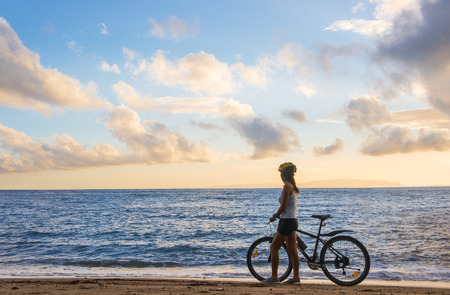 Young asian woman with bicycle in the beach at sunrise