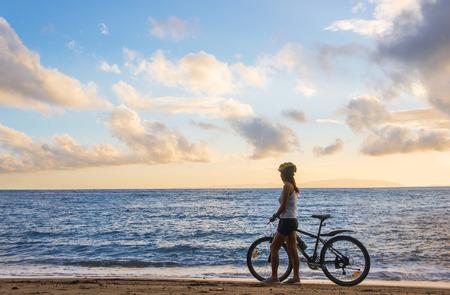 bicicleta: Mujer asiática joven con la bicicleta en la playa al amanecer