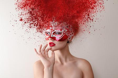 carnival: Modelo de moda joven con máscara de carnaval y la explosión de peinado en polvo