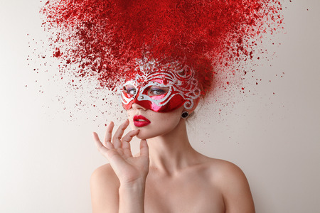 Young fashion model with carnival mask and exploding powder hairstyle