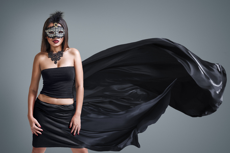 elegant party: Beautiful young woman in mysterious venetian carnival mask. Fashion photo Stock Photo