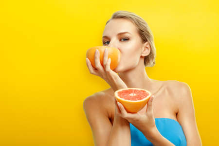 natural face: Young woman with fresh fruits on bright orange background