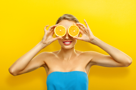 Young woman with fresh fruits on bright orange background