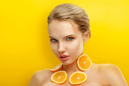 summer fruit: Young woman with fresh fruits on bright orange background