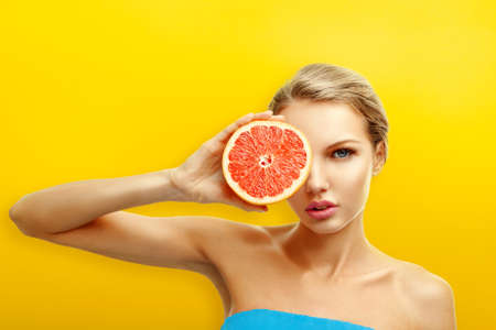 Young woman with fresh fruits on bright orange background photo