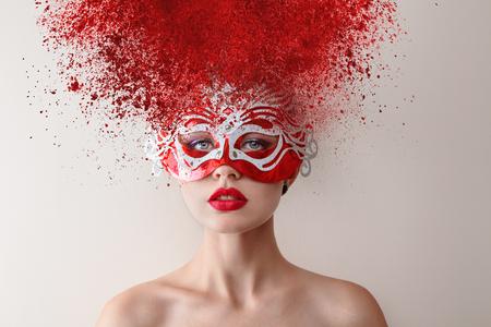 flour: Modelo de moda joven con máscara de carnaval y la explosión de peinado en polvo