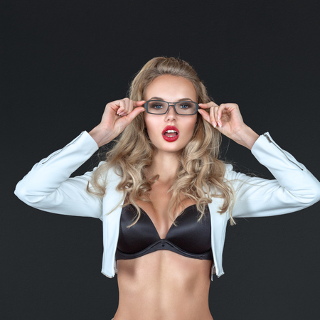 Sexy young blonde woman portrait in studio over dark background photo