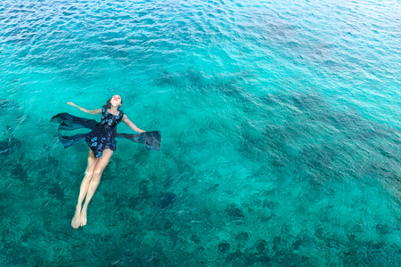Young slim woman lie on back and relaxing in blue sea water fashion shot
