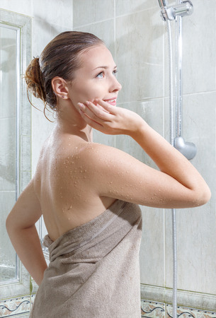 showering: Young beautiful smiling woman in towel with wet hair after taking shower