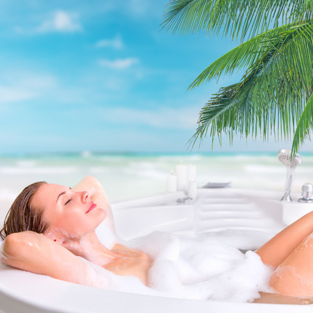 lying in bathtub: Young beautiful woman enjoying bath at the resort in outdoor whirlpool bathtub