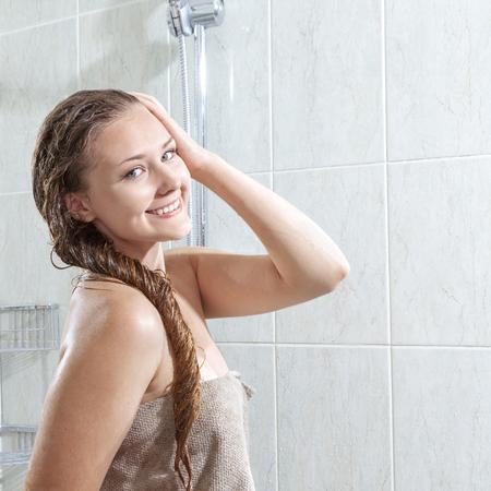 mujer bañandose: hermosa mujer joven y sonriente en una toalla con el pelo mojado después de la ducha