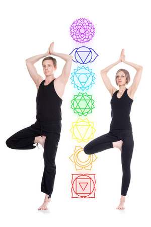 tree position: Young man and woman doing yoga and meditating in tree position with chakras isolated on white background