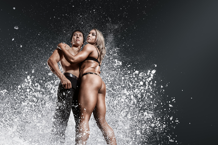 strong woman: Bodybuilder athletic man and woman showing muscles with powerful powder explosion cloud Stock Photo